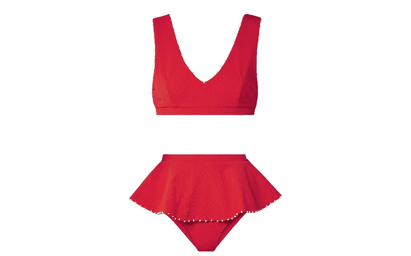 Sembra quasi un abitino il bikini rosso di Marysia che propone un top con scollo a V e spallina larga  abbinato agli slip con gonnellina  (178 euro cadauno).