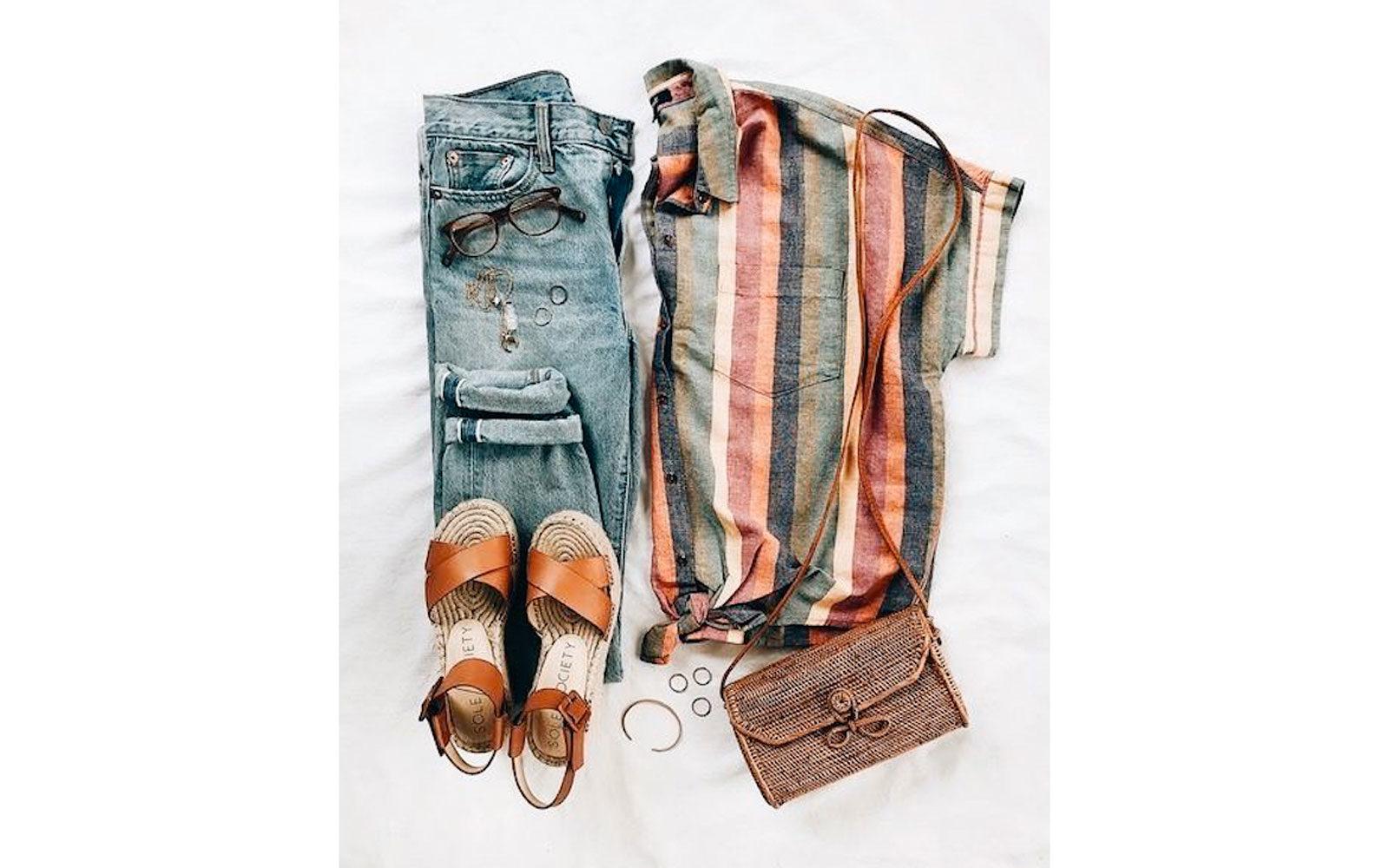 Outfit basico con jeans sandaletti in cuoio e corda pochette in raffia