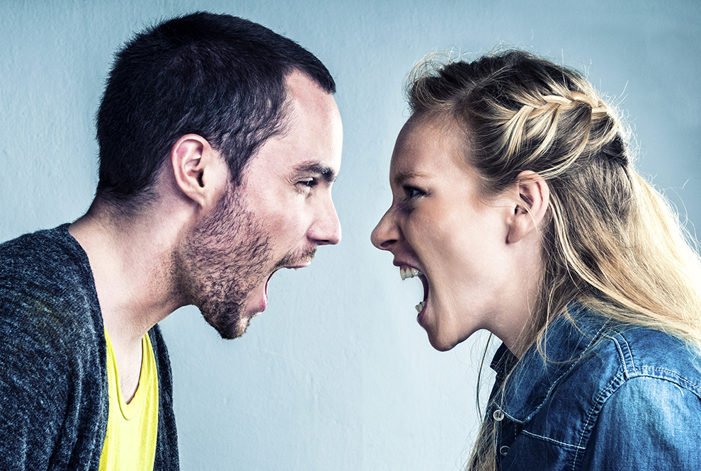 A young man and a young female have a big argument . They are yelling at each other.