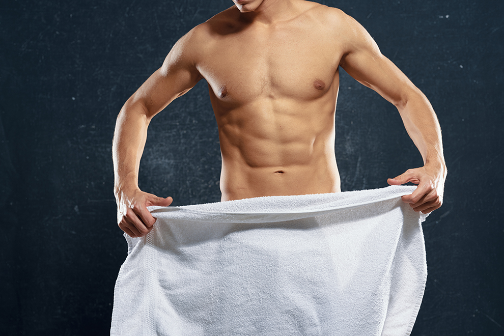 A man with a naked torso holds a towel in his hands                        ; Shutterstock ID 1299235177